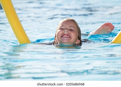Child in blue water of the swimming pool. Girl, happiness.