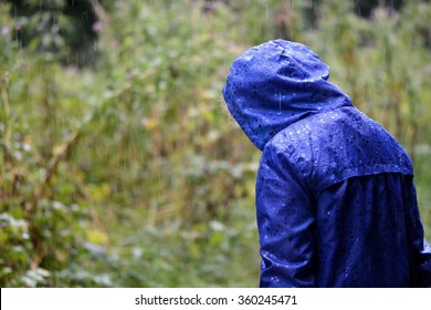 Child in a blue waterproof coat in the rain. A girl stands with her head bowed in heavy rain, in a bright blue raincoat