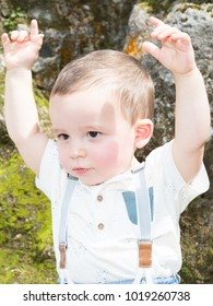 a child with both arms raised in park