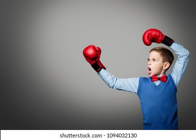 Child in Boxing Gloves, Elegant Kid Boy Boxer Raised Arms Up, Young Fighter over Gray Background, People Power Concept