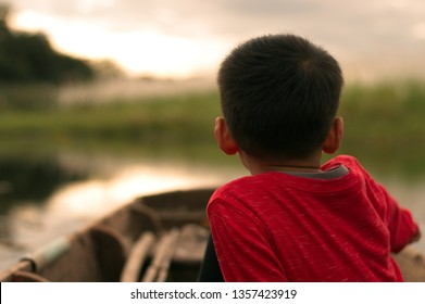 child boy Asian looking grass Poaceae field turn one's back on sit in boat portrait wearing red T shirt  long sleeve golden sky