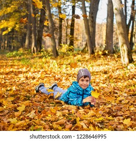 Child boy in autumn park with falling leaves.. He lies on the yellow leaves.