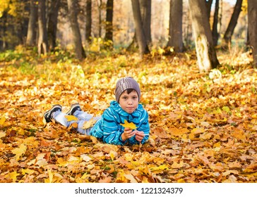 Child boy in autumn park with foliage. He lies on the yellow leaves.
