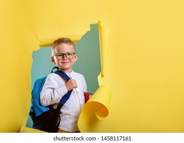 Child boy with book and bag breaking through yellow paper wall.