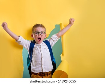 Child boy with book and bag breaking through yellow paper wall. Happy smiling kid go back to school, kindergarten. Portrait of success boy with raising hands up. Fashion, power, winner