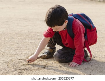 Child boy drawing into sand with a wood stick