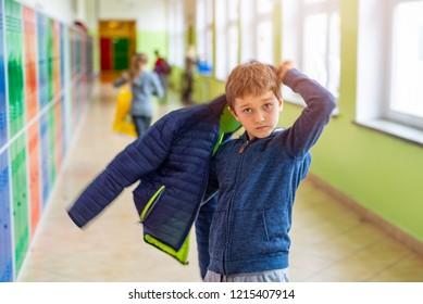 Child boy dressing his autumn jacket in school locker room
