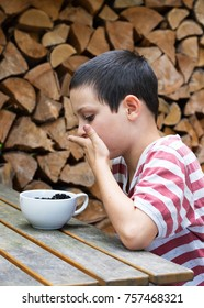 Child boy eating blackberries from a bowl at wooden garden table.