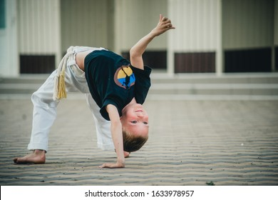 child boy engaged in capuero on the street
