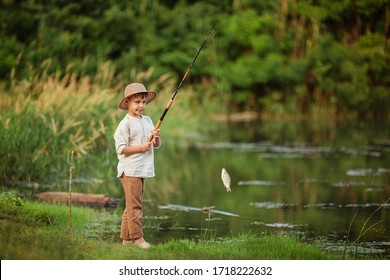 child boy engaged in fishing hobbies. he stands on the riverbank in the summer and holds a fishing rod with caught fish