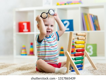 child boy with eyeglasses playing abacus toy in nursery