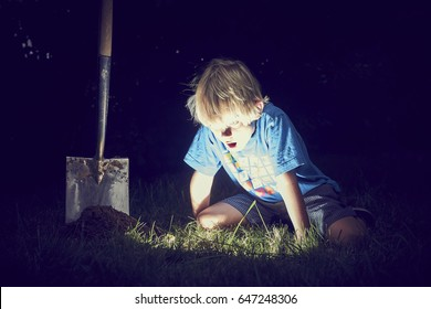 Child boy found glowing treasure in the ground. Boy over a dugout glowing hole in the earth with a shocking look on his face. Color effect added