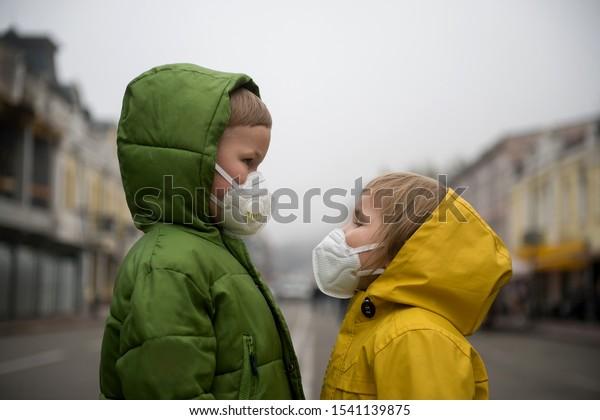 Niños y niñas caminan afuera con protección de máscara facial. Niños de escuela respirando con máscara médica debido al smog y la contaminación del aire. Niños con abrigo amarillo brillante.