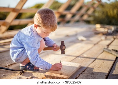 Child (boy) hammers nails with a hammer  in a wooden board on the roof