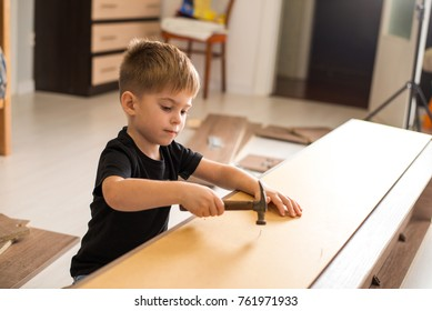 Child (boy) hammers nails with a hammer. assembling furniture at home