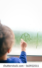 Child boy with hand draws on cold fogged window, closeup image. back view, blur sun light background