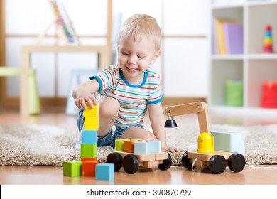 Child boy is happy to play toy building blocks and loader car