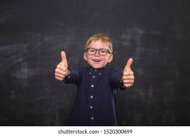 Child boy happy smiling kid go back to school, kindergarten. Success, motivation, winner, genius concept. Little kid dreaming to be superhero