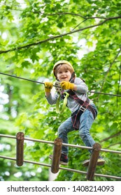 Child boy having fun at adventure park. Go Ape Adventure. Cargo net climbing and hanging log. Early childhood development. Artworks depict games at eco resort which includes flying fox or spider net