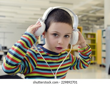 Child boy with headphones listening music or audio in a classroom or library room