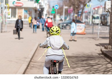 Child boy with helmet riding on a cycle path at the city street