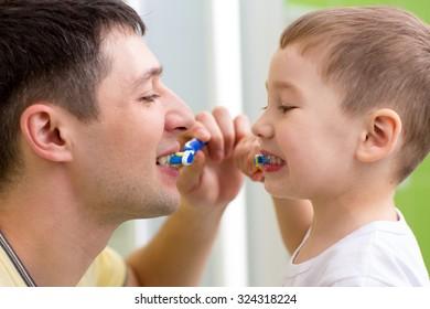 child boy and his dad brushing teeth in bathroom