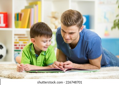 child boy and his dad read a book on floor at home
