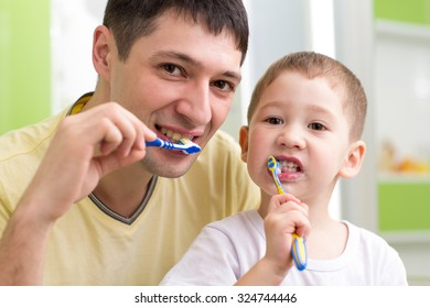 child boy and his father brushing teeth in bathroom