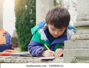 Child boy holding a pen and writing or drawing on paper about what he find on the way to forest, Schoo kid exploring with school trip,Children learning about seasons change on spring,Lean from nature.