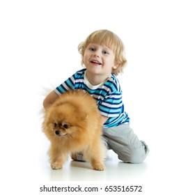Child boy hugging dog spitz, isolated on white background