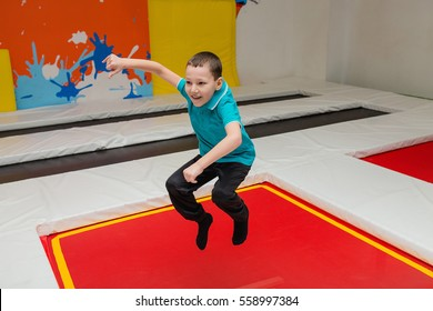 Child boy jumping on trampoline in fly park
