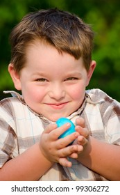 Child Boy kid holding colorful Easter Egg after finding it during hunt