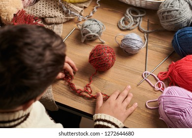 Child boy is learning to knit. Colorful wool yarns are on the wooden table. They are placed as smiling face. Hand closeup.