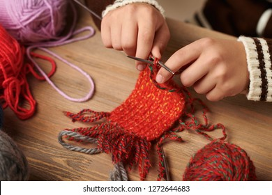 Child boy is learning to knit. Colorful wool yarns are on the wooden table. Hand closeup.