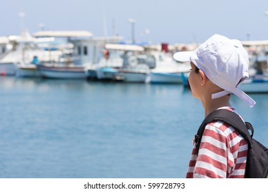 Child boy looking at boats and yachts in a port or harbor, traveling or holiday concept.