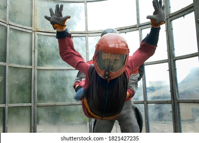 Child boy with man instructor is flying in aerodynamic tube. Instructor is holding boy by the special suit. Professional lesson in air tube for newcomers. Wearing in helmet and costume.