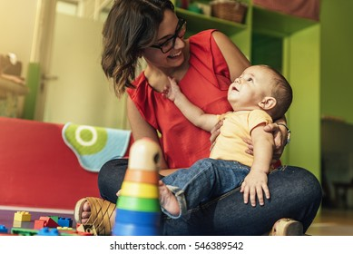 Child boy and mother playing with educational toy.