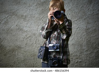 Child boy photographer with many cameras around his neck.