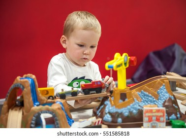 Child boy play with wooden train, build toy railroad at home or daycare. Toddler boy play with crane and cars. Educational toys for preschool and kindergarten child. indoor playground