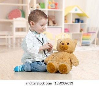 child boy playing doctor and curing plush toy indoors