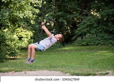 Child boy playing on a zip line swing in the park in summer.
