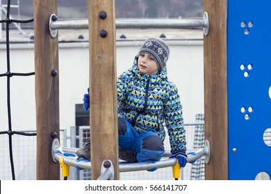 Child boy playing in playground on cold winter day.