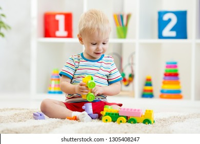 Child boy playing toys at home or kindergarten