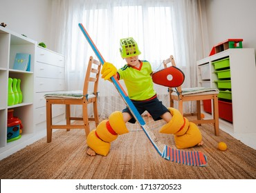 child boy plays hockey home having made form with his own hands from improvised tools gate made of chairs. Home improvisation children resourcefulness games home kids sport home quarantine