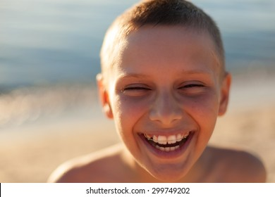 child boy portrait close up sunset backlight happy laughing braces teeth selective focus