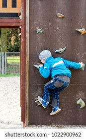 Child boy in a publick playground climbing a glimbing wall.