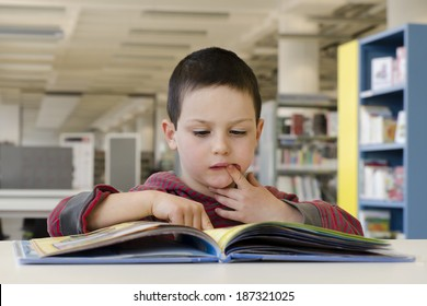 Child boy reading a book in a public library room.