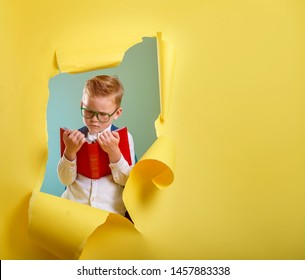 Child boy reading a book  while breaking through yellow paper wall. Smart kid go back to school, kindergarten. Success, motivation, winner, genius concept. Little kid dreaming to be superhero