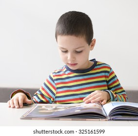 Child boy reading a large pickture book at a desk or table book