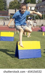 Child boy running and jumping over hurdle at school sport day.